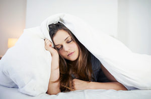young woman looking tired in bed